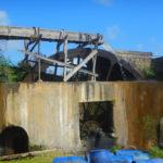 Roue entrainée par de l'eau de la rivière qui entraine la machine à broyer les cannes à sucre